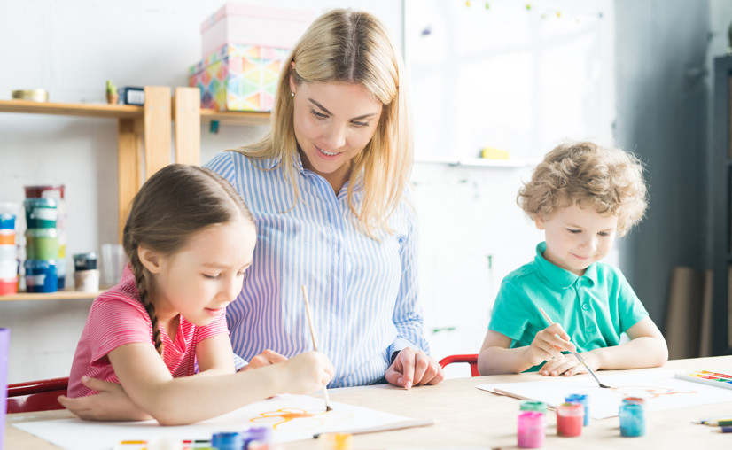 Two kids, boy and girl, painting together with their art teacher at the table at art class